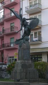 La statua raffigura un angelo con la spada in mano. Sui quattro lati della base sono riportati i nomi di coloro che diedero la vita per l' Italia . Sembra che una copia in miniatura si trovi alla Casa Bianca negli USA.